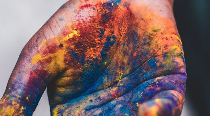photo of person s hand with paint colors